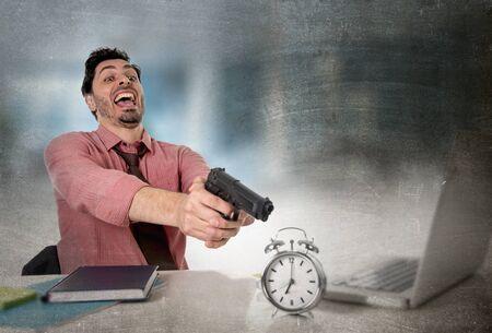adentro y afuera: joven atractivo hombre de negocios en el estr�s en el escritorio de la computadora de oficina que se�ala el arma de mano con el reloj de alarma en el tiempo y plazo proyecto empresarial concepto vencimiento en enojado expresi�n facial frustrado