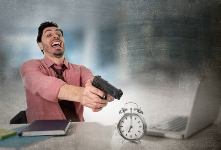 expiring: young attractive businessman in stress at office computer desk pointing hand gun to alarm clock in out of time and business project deadline expiring concept in angry frustrated face expression Stock Photo