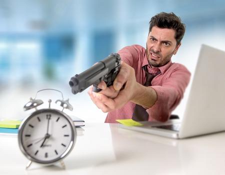 adentro y afuera: joven atractivo hombre de negocios en el estrés en el escritorio de la computadora de oficina que señala el arma de mano con el reloj de alarma en el tiempo y plazo proyecto empresarial concepto vencimiento en enojado expresión facial frustrado