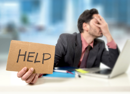 overwork: young businessman at office desk working on computer laptop asking for help holding cardboard sign looking desperate and depressed in business stress overwhelmed and overwork concept