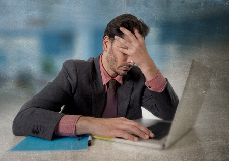 business problems: young attractive businessman sitting at office desk working on computer laptop covering his face desperate and worried in work stress and business problems concept grunge edit Stock Photo