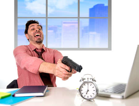 project deadline: young attractive businessman working at computer desk pointing hand gun to alarm clock in out of time and business project deadline expiring concept angry and frustrated in business district office