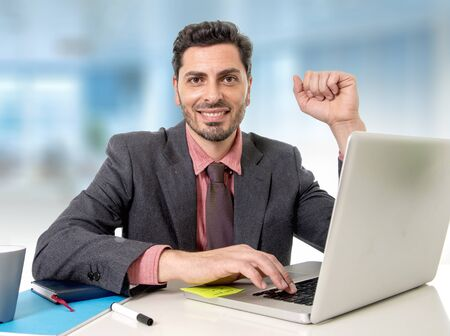 stubbly: young handsome businessman  working at office computer laptop looking happy satisfied and relaxed in business and work success concept isolated on white background Stock Photo