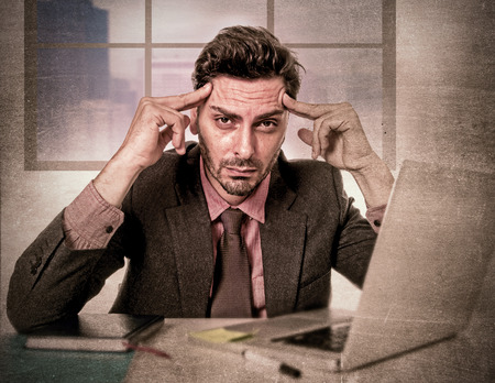 headache man: young attractive businessman sitting at office desk working on computer laptop depressed and desperate suffering headache looking frustrated and sad in grunge dirty edition background
