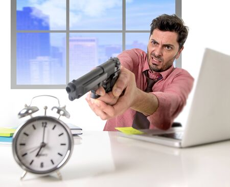 expiring: young attractive businessman working at computer desk pointing hand gun to alarm clock in out of time and business project deadline expiring concept angry and frustrated in business district office