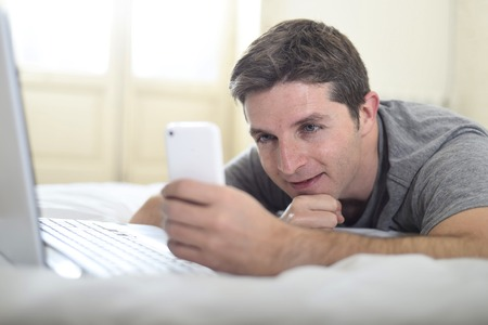 cell phone addiction: close up portrait of young attractive man lying on bed or couch using mobile phone and computer laptop working from home in internet addiction and modern lifestyle concept