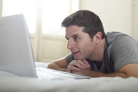work addicted: close up portrait of young attractive man lying on bed watching on line movie in computer laptop at home in internet and modern lifestyle concept