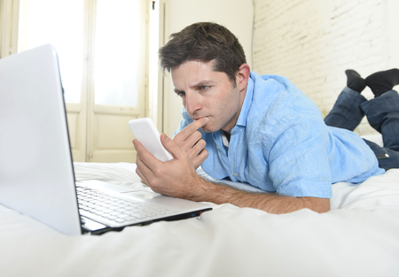 mobile internet: young attractive man lying on bed or couch using mobile phone and computer laptop working from home in internet business and modern lifestyle concept Stock Photo