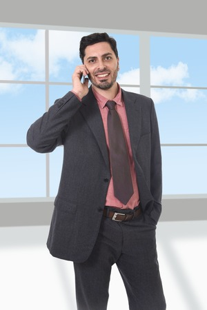 hispanic ethnicity: corporate full body portrait of young attractive businessman of Latin Hispanic ethnicity talking on mobile phone in suit and tie standing in front of modern office window Stock Photo