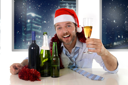 glass bottle: drunk happy business man in Santa hat with alcohol bottles in new year toast with champagne glass smiling drinking too much at Christmas party at night in the office