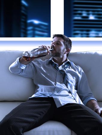 borracho: Atractivo hombre de negocios borracho sentado en el sof� desperdicia bebiendo whisky directamente de la botella en el problema del alcoholismo, el abuso de alcohol y concepto de adicci�n en busca del grunge en la noche en el apartamento moderno o la oficina