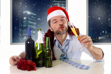 drinking drunk: drunk happy business man in Santa hat with alcohol bottles in new year toast with champagne glass smiling drinking too much at Christmas party at night in the office
