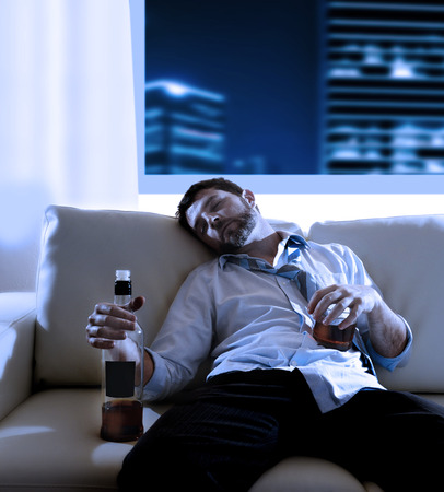 wasted: Attractive drunk business man sitting on couch wasted  drinking whiskey bottle in alcoholism problem , alcohol abuse and addiction concept looking grunge at night in modern apartment or office
