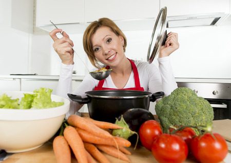 home cooking: young happy and attractive home cook woman in red apron at domestic kitchen holding saucepan tasting hot soup vegetable stew smelling delicious in lifestyle and amateur cooking success Stock Photo