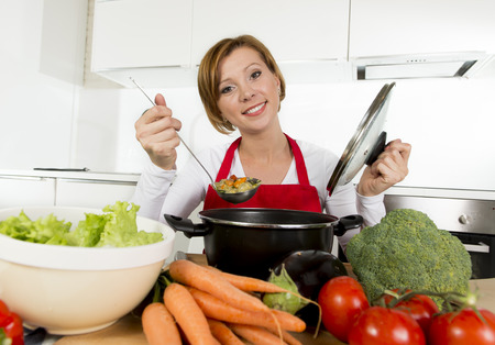 hot soup: young happy and attractive home cook woman in red apron at domestic kitchen holding saucepan tasting hot soup vegetable stew smelling delicious in lifestyle and amateur cooking success Stock Photo