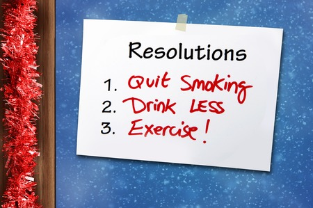 frame less: New year Resolutions Handwritten Note for a Healthy Life with quit smoking drink less and doing exercise stack on window glass with Christmas tinsel frame