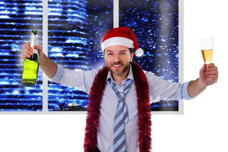 Happy attractive business man wearing santa hat with tinsel around neck in blue shirt and loose tie holding bottle and glass of champagne drinking at Christmas party in office at night