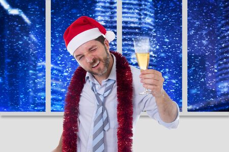 drunk happy attractive business man wearing santa hat with tinsel around neck in blue shirt and tie holding bottle and glass of champagne drinking at christmas party in office at night