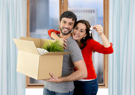 rent: young happy Hispanic couple moving together in a new flat or apartment carrying cardboard boxes home belongings holding house key smiling in housing and real state concept Stock Photo
