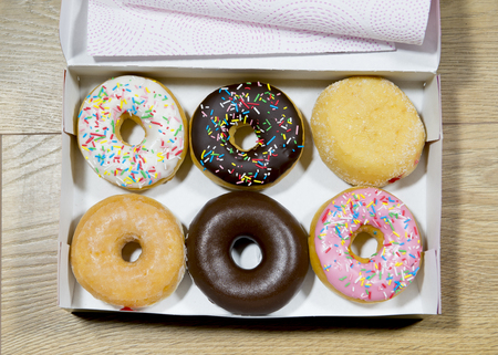 boxed: opened box with a donut set in various flavors such as chocolate strawberry cream and candy toppings looking delicious  in sugary breakfast and sugar abuse nutrition concept
