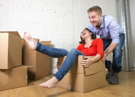 parejas romanticas: young happy American couple unpacking having fun enjoying together moving in a new house or flat playing with woman or wife inside cardboard box and husband or boyfriend pushing in real estate concept