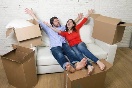 Renting: young happy American couple lying on couch unpacking boxes having fun together celebrating moving in a new house or apartment flat in mortgage renting and real estate concept