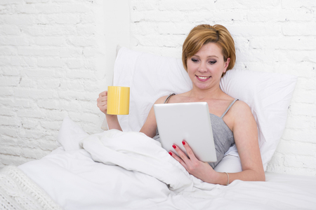 sleeping pad: young attractive red hair girl in sleeping tank top and pajamas pants lying happy on bed at home using digital tablet pad for reading morning online news in internet while having coffee for breakfast