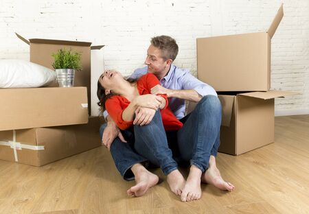 unpacked: young happy couple sitting on the floor with unpacked cardboard boxes celebrating moving in a new house or apartment flat in real estate mortgage and independent lifestyle concept Stock Photo