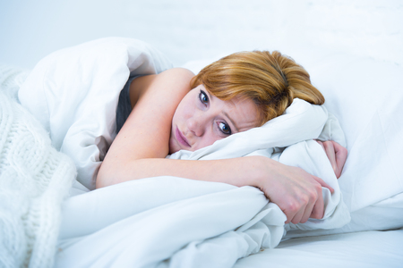 eyes wide: young attractive woman in sad and depressed face expression with eyes wide open lying in bed looking sick and unable to sleep suffering depression , nightmares or insomnia sleeping disorder