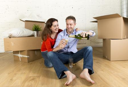 jonge gelukkige Amerikaanse paar zittend op de vloer uitpakken van dozen samen vieren met champagne toast bewegen in een nieuw huis of appartement in onroerend goed en onafhankelijk lifestyle concept