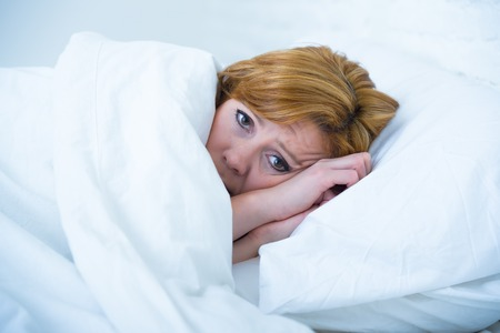 eyes wide open: young attractive woman in sad and depressed face expression with eyes wide open lying in bed looking sick and unable to sleep suffering depression , nightmares or insomnia sleeping disorder