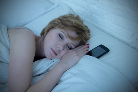 cell phone addiction: young attractive woman sleeping in bed alone holding mobile phone next to her at night dim blue light in social network internet and smart phone addiction concept Stock Photo