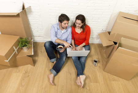house moving: young happy American couple sitting on floor moving in a new house or apartment flat using computer laptop choosing online furniture and household in real estate and independent lifestyle concept