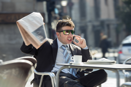 bad news: young attractive businessman sitting outdoors on street bar having coffee cup for breakfast holding newspaper angry and upset as if reading bad news  talking on mobile phone Stock Photo