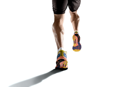 calves: close up view strong athletic legs with ripped calf muscle of young sport man running isolated on white background with copy space in sport fitness endurance and high performance concept