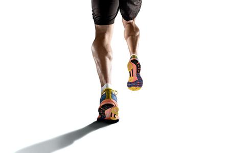 Sluit omhoog mening sterke atletische benen met gescheurde kuitspier van de jonge sport man loopt op een witte achtergrond met een kopie ruimte in de sport fitness uithoudingsvermogen en high performance-concept Stockfoto