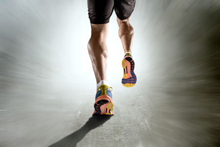 athlete: close up view strong athletic legs with ripped calf muscle of young sport man running isolated on motion grunge background in sport fitness endurance and high performance concept Stock Photo