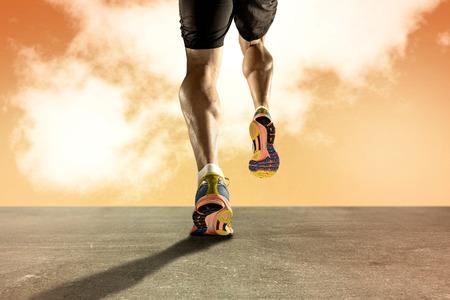 hombres corriendo: Cierre de vista fuertes piernas atléticas con músculo de la pantorrilla arrancado de deporte hombre joven que se ejecutan en la carretera de asfalto grunge en el cielo del atardecer naranja en la resistencia de la aptitud del deporte y el concepto de alto rendimiento