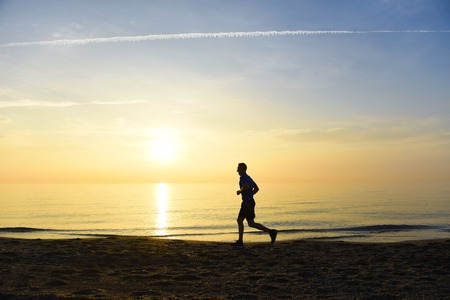 nature silhouette: silhouette of young sport man running outdoors on beach at golden color sunset with orange and purple sky in front of the sea in fitness and healthy lifestyle concept