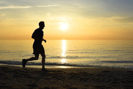 male silhouette: silhouette of young sport man running outdoors on beach at golden color sunset with orange and purple sky in front of the sea in fitness and healthy lifestyle concept