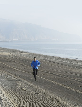 outdoor exercise: young sport man running alone on desert beach along the sea shore training workout on a foggy and overcast winter early morning in fitness and healthy lifestyle concept Stock Photo