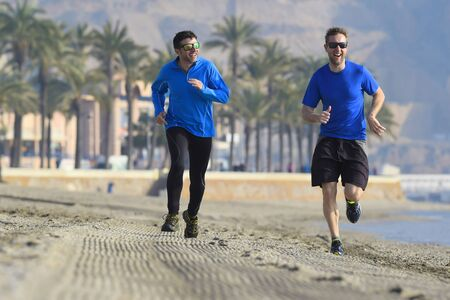 running pants: two men friends running together on beach sand with palm trees background in morning training session jogging workout one in long sleeve and pants the other guy in shorts Stock Photo