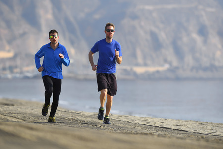 running pants: two men friends running together on beach sand with beautiful coast mountain background in morning training session jogging workout one in long sleeve and pants the other guy in shorts