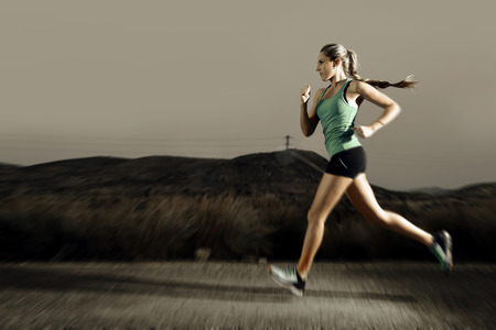 road runner: young attractive and fit sport woman running outdoors on asphalt road in mountain landscape on evening with harsh light in fitness workout training shot in motion blurred advertising style
