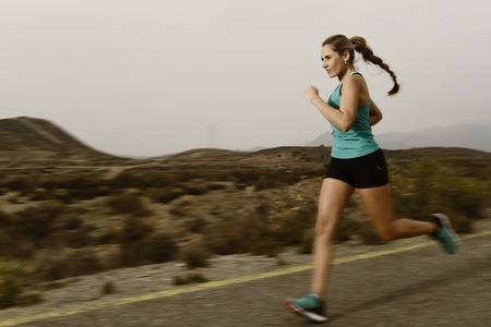 harsh light: young attractive and fit sport woman running outdoors on asphalt road in mountain landscape on evening with harsh light in fitness workout training shot in motion blurred advertising style