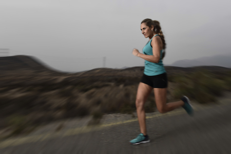 harsh: young attractive and fit sport woman running outdoors on asphalt road in mountain landscape on evening with harsh light in fitness workout training shot in motion blurred advertising style
