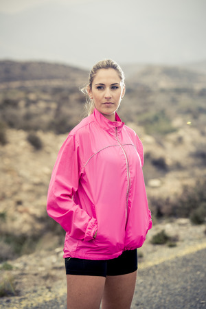 defiant: young attractive sport woman in running pink jacket posing with attitude defiant and cool in asphalt road in front of mountain desert landscape in body fitness and healthy lifestyle concept Stock Photo