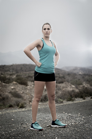 defiant: young attractive sport woman in running singlet and shorts posing defiant and cool in asphalt road in front of mountain desert landscape in body fitness and healthy lifestyle concept