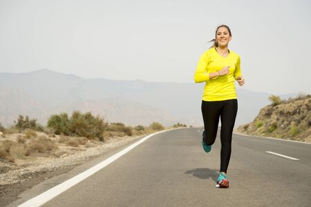 jogging: young attractive sport woman running on asphalt road with desert mountain landscape background looking happy and healthy in jogging training workout , fitness and wellness concept