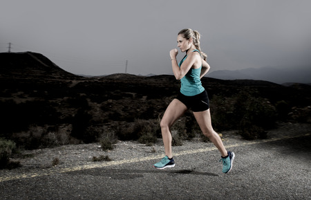girl action: young attractive and fit sport woman running outdoors on asphalt road in mountain landscape on evening with harsh light in fitness workout training shot in motion blurred advertising style